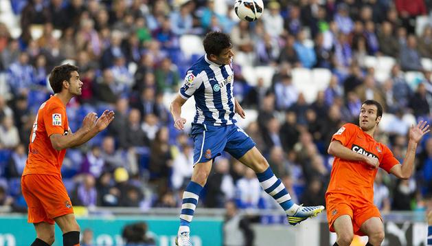 El defensa del Espanyol Héctor Moreno cabecea ante la mirada de dos rivales de la Real Sociedad