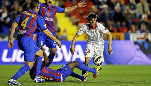 El sevillista Coke trata de llevarse el balón entre tres jugadores del Levante
