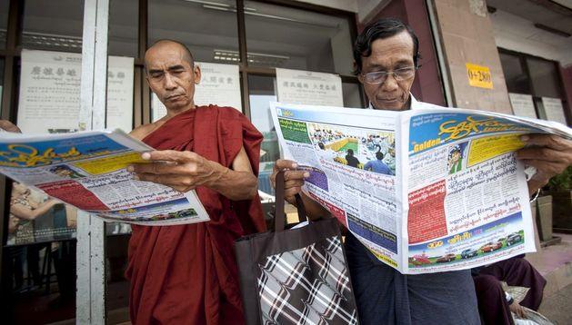 Dos hombres leen periódicos en Rangún (Birmania)