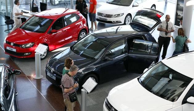 Personas miran coches en un concesionario