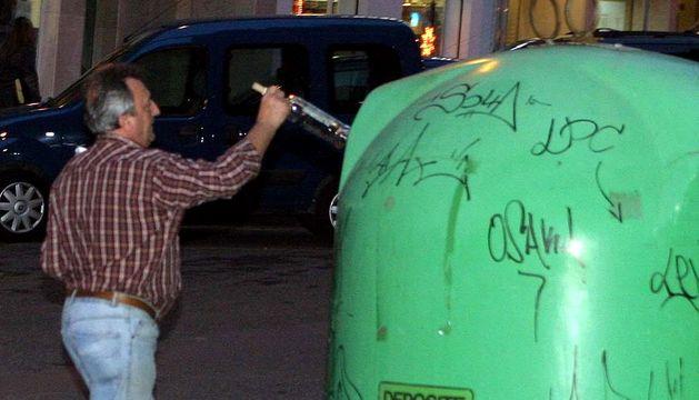 Un hombre deposita una botella en el contenedor de vidrio