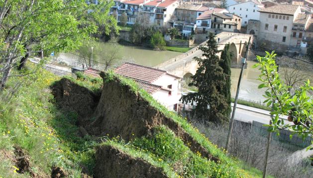 En primer plano el deslizamiento de tierra, al fondo la vivienda desalojada