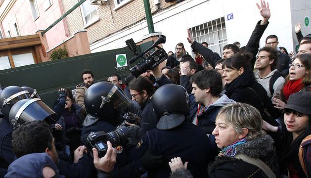 Efectivos de la policía junto a las personas concentradas esta tarde para realizar un escrache, ante la que creen que es la vivienda de la vicepresidenta