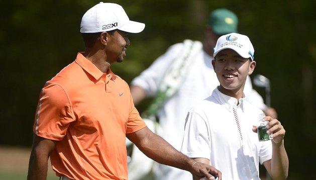 Tiger Woods (i) y el chino Tianlang Guan (d), de tan sólo 14 años, se alejan del hoyo 11 durante una práctica previa al Torneo de Maestros en el Club de Golf Nacional de Augusta, Georgia (EE.UU.). El evento será del 11 al 14 de abril