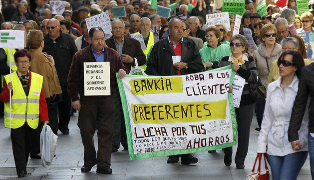 Un numeroso grupo de personas afectados por las participaciones preferentes de Bankia, a su paso por la plaza madrileña de Callao.