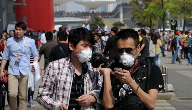 Dos ciudadanos caminan por la calle en Shanghai protegidos con máscaras para evitar el contagio de la nueva cepa de gripe aviar