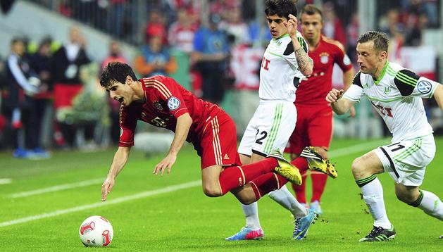 Javi Martínez cae ante la presión de los jugadores del Wolfsburgo, Fagner (centro) y Ivica Olic (dcha.)