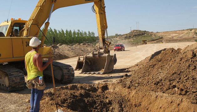 Un trabajador junto a una excavadora en las obras del TAV entre Castejón y Cadreita.