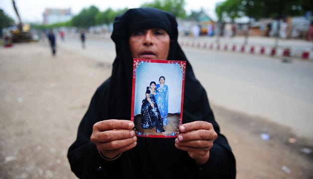 Una mujer sujeta la imagen de su hermana desaparecida.