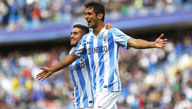 El delantero paraguayo del Málaga Roque Santa Cruz (dcha.) celebra, junto al centrocampista chileno Pedro Morales