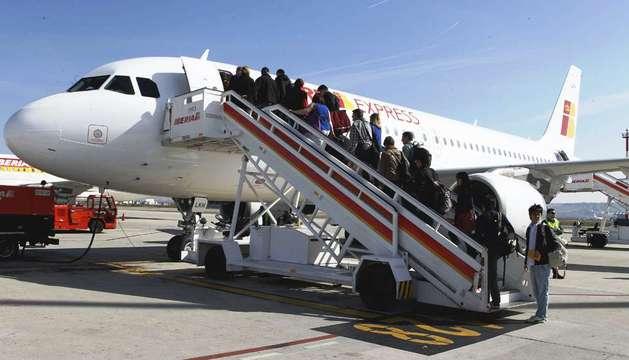 Pasajeros acceden a un avión de Iberia Express en el aeropuerto madrileño de Barajas