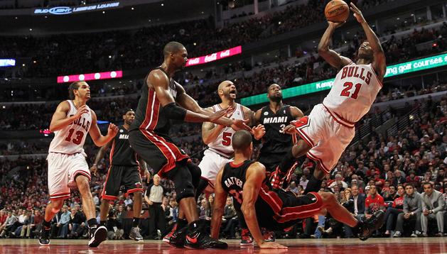El jugador de los Bulls, Jimmy Butler, trata de encestar ante la defensa del jugador de Miami Heat, Shane Battier