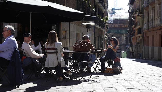Varias personas aprovechan el sol en un establecimiento del Casco Viejo de Pamplona