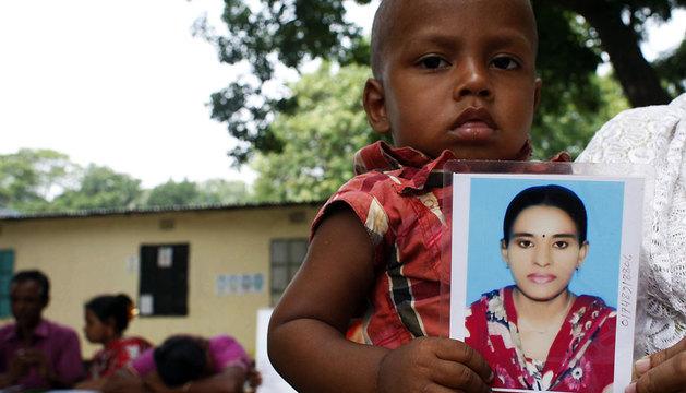 Una niña de dos años sostiene una fotografía de su madre desaparecida en el derrumbe de la fábrica textil en la localidad de Dacca.