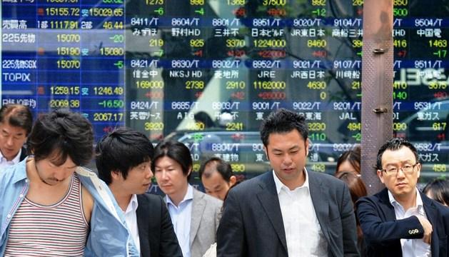 Peatones pasan junto a un panel de datos económicos en Tokio.