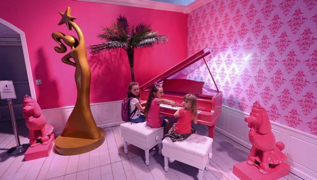 Tres niñas tocan un piano rosa en el interior de la casa de Barbie.