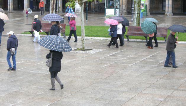 Los pamploneses pasean por la Plaza del Castillos bajo sus paraguas.