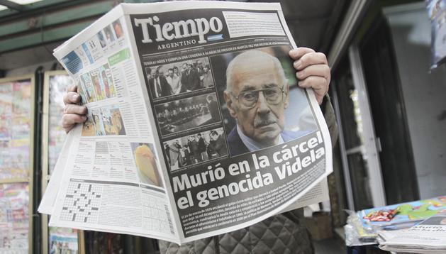 Un hombre lee un periódico con la noticia de la muerte del exdictador argentino Jorge Rafael Videla