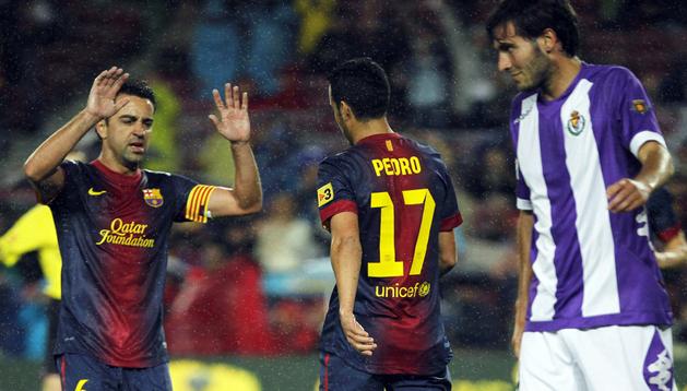 El delantero del Fútbol Club Barcelona Pedro Rodríguez (2º por la dcha.) celebra con su compañero Xavi Hernández (izda.) el gol marcado al Real Valladolid