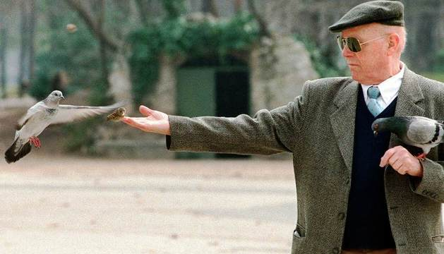 Un anciano da comida a las palomas mientras pasea.