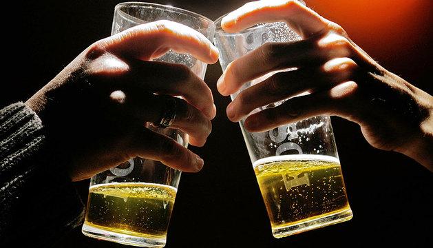 Dos personas brindan con cerveza.