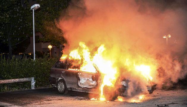 Vista de un vehículo en llamas tras los disturbios registrados en el barrio de Kista, en Estocolmo.