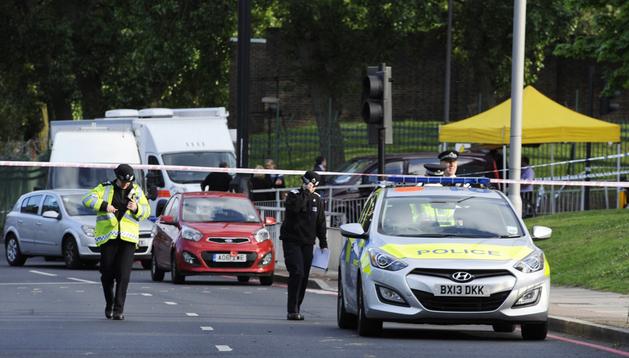 Varios policías británicos inspeccionan el lugar donde un soldado murió y otros dos resultaron heridos en un ataque con machete en Londres