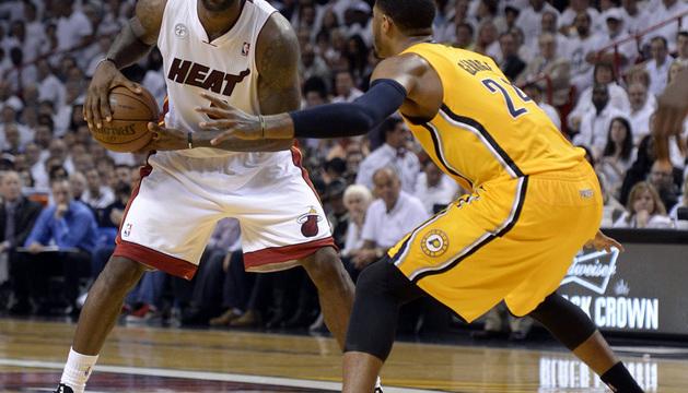 LeBron James (i) de los Heat en acción ante Paul George (d) de los Pacers durante un partido.