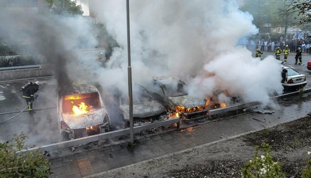Bomberos extinguen el fuego en un carro incendiado después de disturbios, originados por jóvenes en diferentes suburbios alrededor de Estocolmo