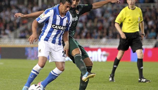 El centrocampista alemán del Real Madrid Sami Khedira (d) pelea un balón con el delantero uruguayo de la Real Sociedad, Diago Ifrán