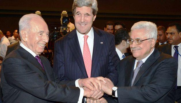 Simon Peres, John Kerry y Mahmoud Abbas se saludan durante una reunión en el marco del Foro Económico Mundial.