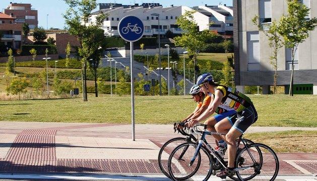 Ciclistas con casco circulando por una carretera de Ripagaina.