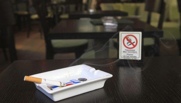 Un cigarro se consume en un cenicero junto a un cartel que indica la prohibición de fumar.