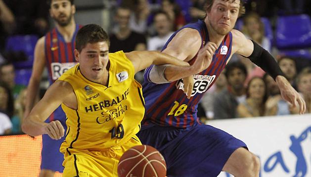 El ala-pívot del Regal FC Barcelona CJ Wallace (dcha.) y el base del Herbalife Gran Canaria Oscar Alvarado durante el primer encuentro