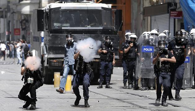 Policías antidisturbios turcos disparan botes de gas lacrimógeno contra los manifestantes.