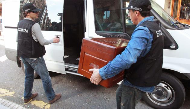 Un policía de la científica de la Ertzaintza porta un baúl del domicilio, tras el registro efectuado esta tarde, del hombre detenido