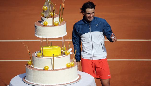 El tenista español Rafael Nadal recibe una tarta con motivo de la celebración de su 27 cumpleaños, tras un partido de octavos de final de Roland Garros que disputó contra el japonés Kei Nishikori en París