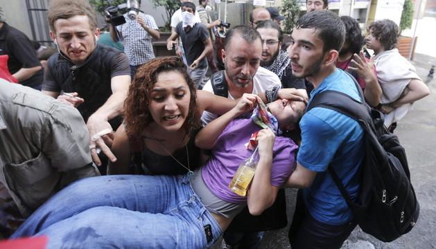 Una manifestante herida es evacuada por varios participantes de la protesta.