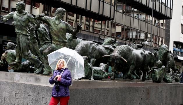 Una mujer, con paraguas junto al monumento al encierro el pasado día 31.