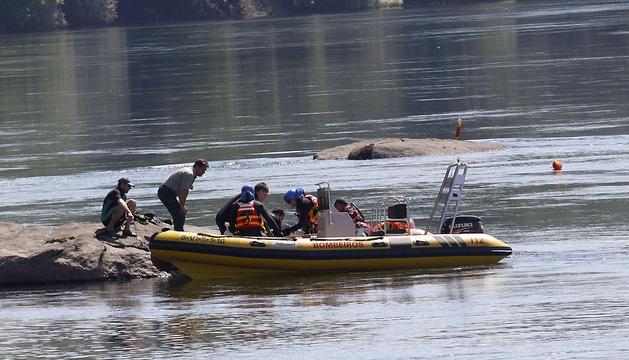 Los equipos de rescate recuperan el cuerpo de uno de los hermanos marroquíes ahogados en el Miño.