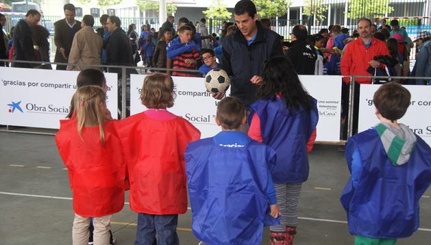 Un voluntario explica a los niños las reglas de una de las actividades durante las actividades celebradas en Aranzadi