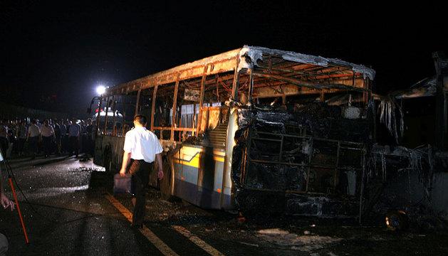 Uno de los investigadores, junto al autobús incendiado.