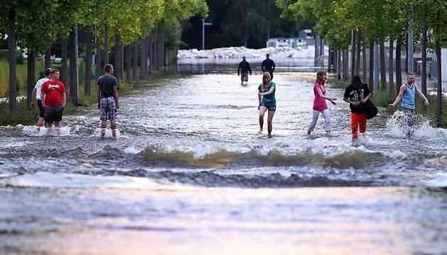 Peatones en una calle de Magdeburg inundada por el Elba.