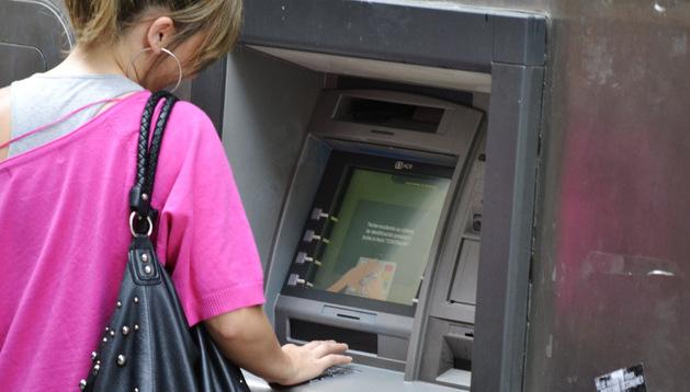 Una mujer extrae dinero de un cajero de una sucursal bancaria en Pamplona