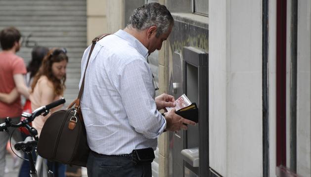 Un hombre extrae dinero de un cajero en Pamplona