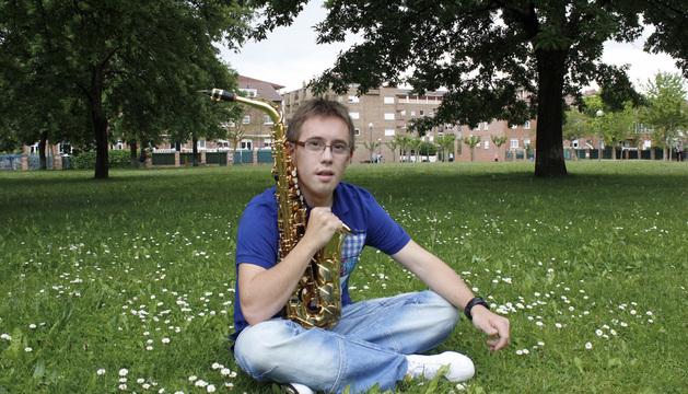 Iñaki posa con su saxofón en el parque del Lago