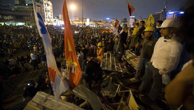 Manifestantes se reúnen sobre una gran barricada.