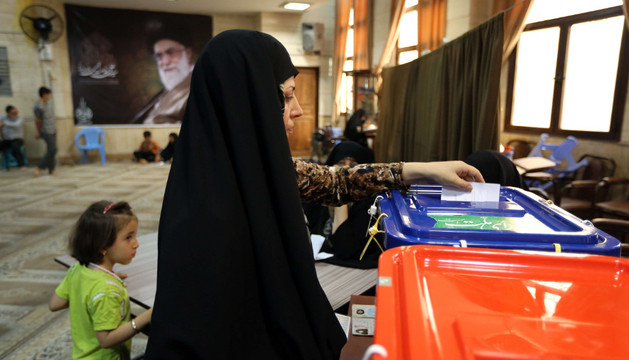Una mujer iraní inserta su voto en una urna.