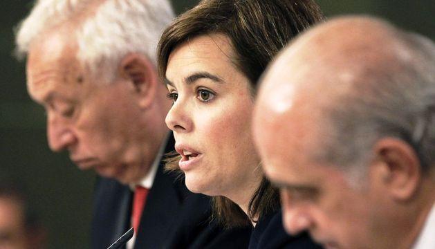 La vicepresidenta del Gobierno Soraya Sáenz de Santamaría (c) y los ministros de Asuntos Exteriores, José Manuel García-Margallo, (iz), y de Interior, Jorge Fernández Díaz, durante la rueda de prensa posterior al Consejo de Ministros.