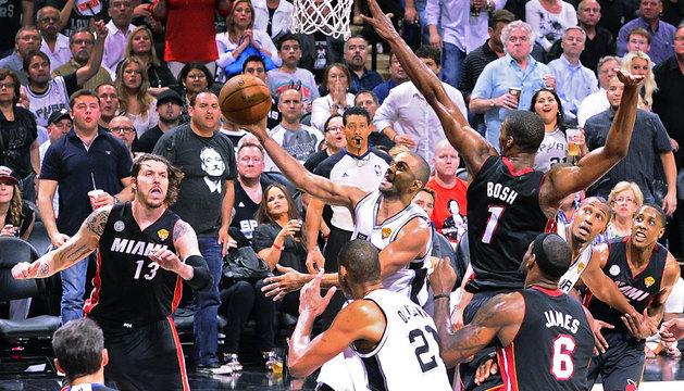 El jugador de los Spurs Tony Parker (c) intenta un lanzamiento ante Chris Bosh (d) de los Heat.